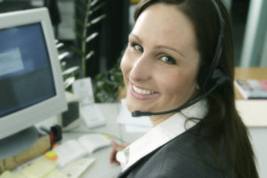 Woman with headset smiling at her computer.