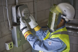 Man with face mask inspecting electric meter