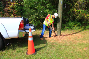 Technician outside testing the base of a wooden pole.